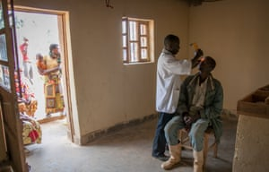 A nurse tests a man's sight at the health centre