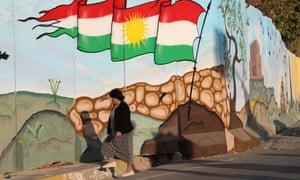 An Iraqi Kurdish woman walks past a mural in Arbil, the capital of the autonomous Kurdish region of northern Iraq