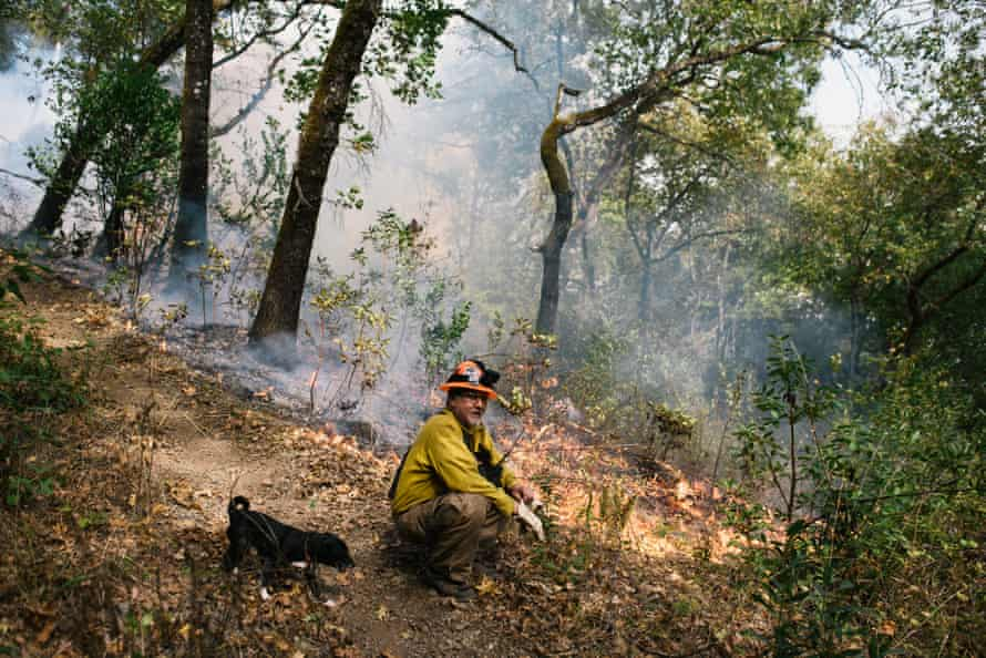 Rick O'Rourke, Yurok fire practitioner and fire and fuels coordinator for the Cultural Fire Management Council, with his dog Puppers during the prescribed burn in Weitchpec.