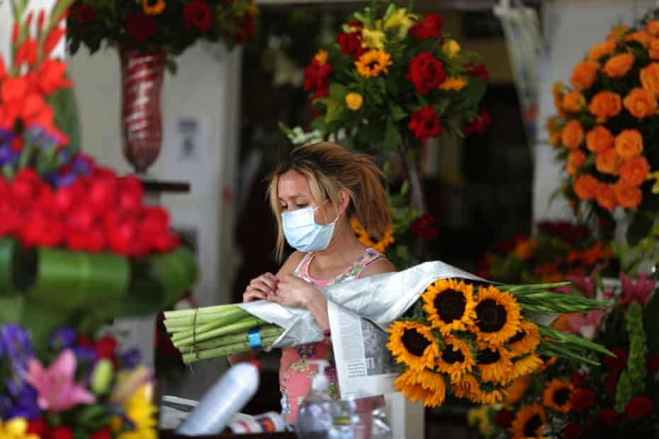A flower seller waits for customers on the first day of the reopening of Los Angeles flower market.