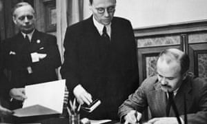 Soviet foreign minister Vyacheslav Mikhailovich Molotov signs the Soviet-German Non-Aggression Pact in Moscow, 23 August 1939. On the left is German foreign minister Joachim von Ribbentrop