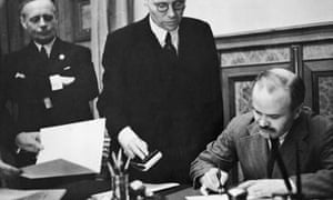 Soviet foreign minister Vyacheslav Mikhailovich Molotov signs the Soviet-German Non-Aggression Pact in Moscow, with German foreign minister Joachim von Ribbentrop looking on, 23 August 1939.