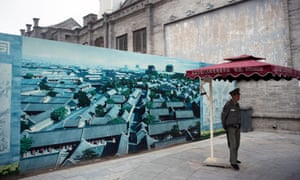A guard stands by the illustration of a project to renovate Beijing's Qianmen street, in 2012.