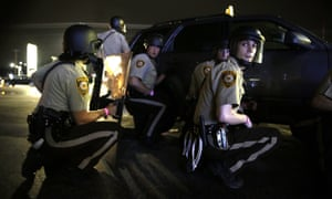 Police take cover behind a vehicle during the protests