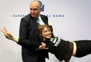 A woman is taken away by security after she interrupted a press conference by President of the European Central Bank (ECB) by throwing confettis following a meeting of the Governing Council in Frankfurt / Main, Germany, on April 15, 2015.