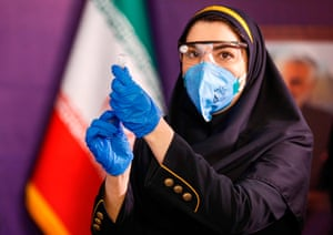 A health worker prepares an injection for a woman during the first trial phase of a locally-made Iranian vaccine for COVID-19 coronavirus disease in Iran's capital Tehran