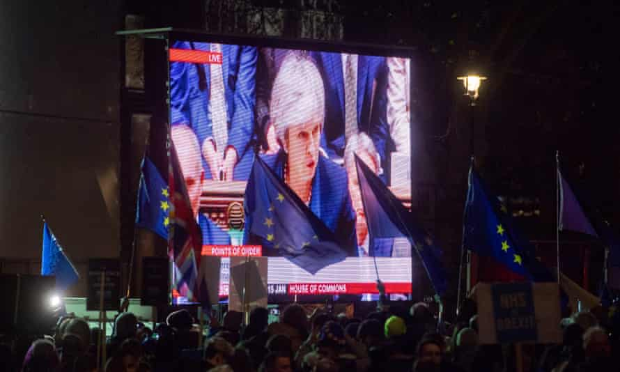 Protesters' flags flutter as video of Theresa May is shown outside the Houses of Parliament, after she was defeated in the vote on the EU withdrawal agreement.