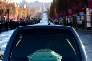The hearse transporting the coffin drives down the Champs-Elysees avenue