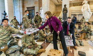 Republicans Vicky Hartzler and Michael Waltz hand pizzas to members of the National Guard on Wednesday.