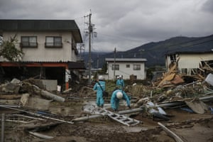 Utility workers survey the damage left by Typhoon Hagibis in the city of Nagano.