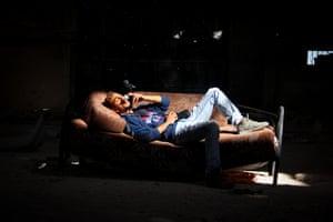 Ahmad smokes, lying on a sofa