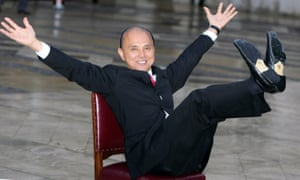 Jimmy Choo sits on a chair his arms out and his legs stretched out