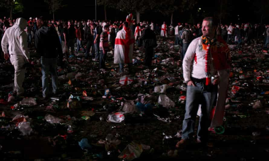 Fans at an outdoor screen near the Eiffel Tower stand dejected among rubbish after watching England lose the 2007 Rugby World Cup Final