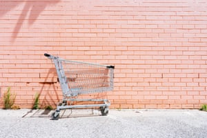Empty shopping cart against a pink brick wall
