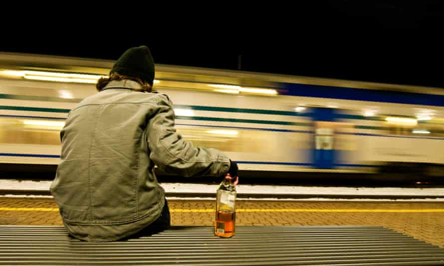 Man on a bench with half empty whisky bottle