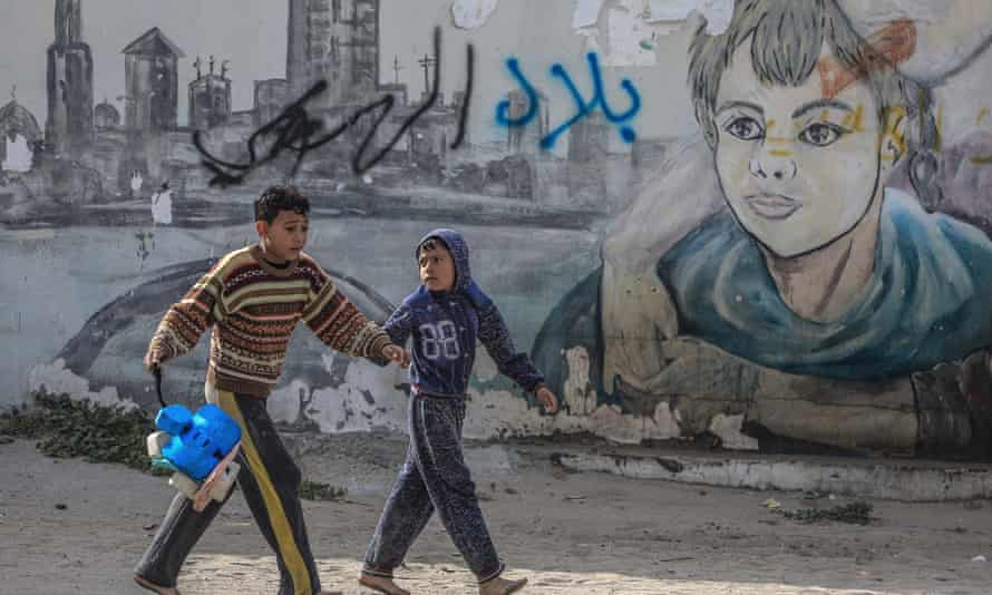 Palestinian refugee boys play in the streets of a refugee camp in Gaza City this month.