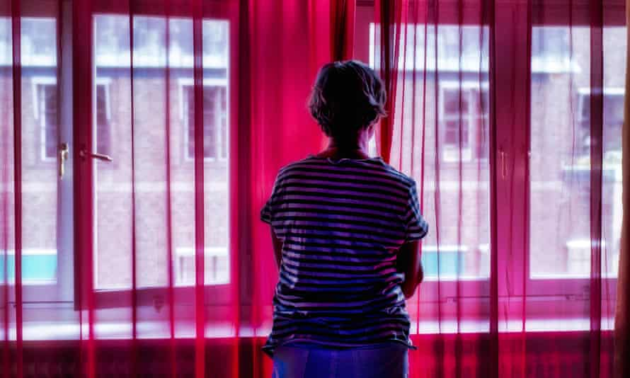 Woman standing alone looking out the window