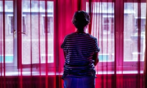 A woman standing alone looking out of the window