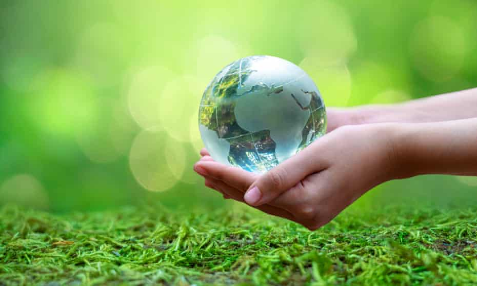 A glass earth held by human hands over a mossy ground