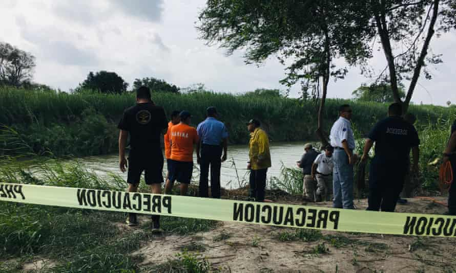 Authorities stand behind yellow warning tape along the Rio Grande where the bodies of Óscar Alberto Martínez Ramírez and his daughter Valeria were found, in Matamoros, Mexico, on Monday.