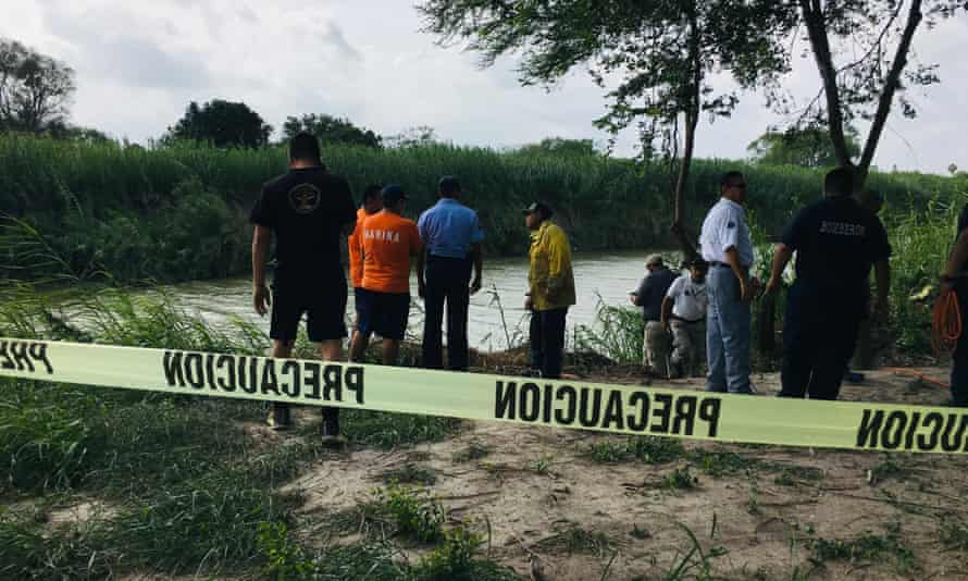Authorities stand behind yellow warning tape along the Rio Grande bank where the bodies of Oscar Alberto Martínez Ramírez and his daughter Valeria were found, in Matamoros, Mexico, on 24 June.