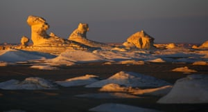 White inselbergs (island mountains) are captured by the setting sun in the White desert