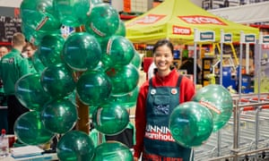 A woman welcoems customers to Bunnings DIY in St Albans with green balloons