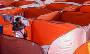 A man wearing a face mask is seen in a modular tent set up for street dwellers to stop the further spread of coronavirus at a sheltered basketball court in Manila, Philippines.