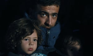A Syrian man waits with his children as they attempt to reach mainland Europe.