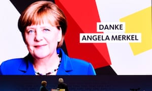 Merkel looks up at a vast sign thanking her for her leadership.