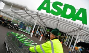 A worker pushes shopping trolleys at an Asda store in west London