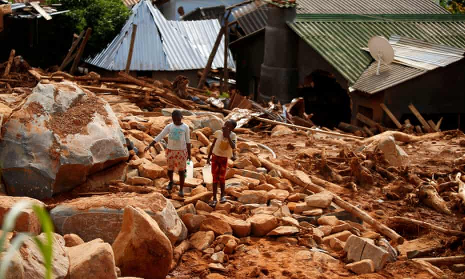 Children carry drinking water over debris created by Cyclone Idai in Chimanimani, Zimbabwe