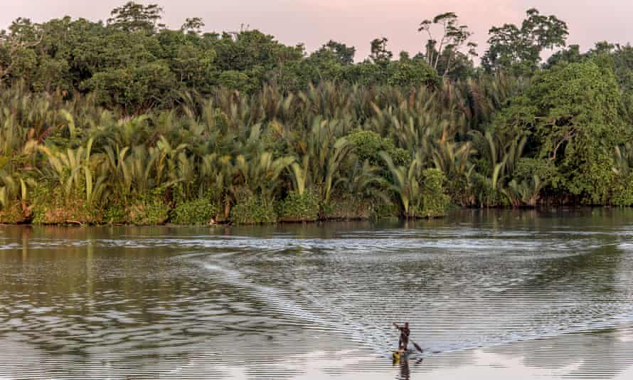 A man and a child paddle in a canoe on the Sepik River in the northern Papua New Guinea.
