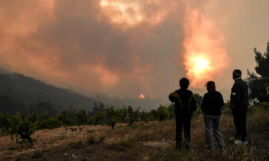 Local residents near the village of Pefkaneas, west of Athens, look as the forest fire rages in Mount Geraneia.