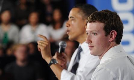 Mark Zuckerberg listens to Barack Obama speak during a town hall meeting in 2011.