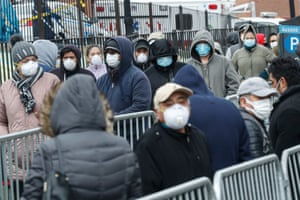 People wear face masks as they wait in line for coronavirus testing at Elmhurst hospital on 25 March.