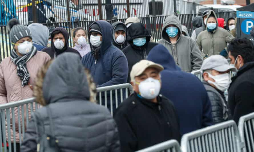 Patients wear personal protective equipment while maintaining social distancing as they wait in line for a Covid-19 test at Elmhurst hospital in New York.