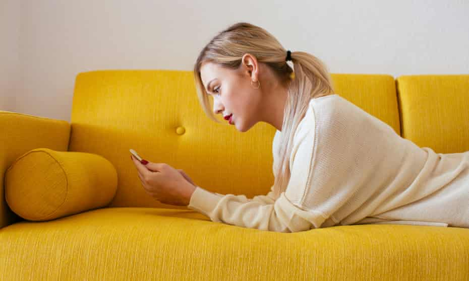 Blonde woman lying on sofa, using smartphone at home