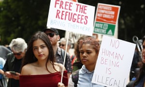 Two woman hold placards at a Sydney rally in support of Manus Island refugees. The Australian Medical Association wants doctors to be allowed to help.