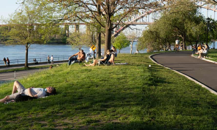 People enjoy the afternoon sun on Sunday at the Astoria Park as temperatures rose amid the coronavirus pandemic in New York City.