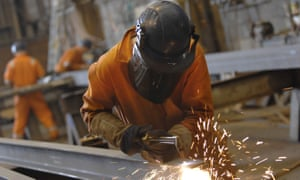 A worker inspects the head of a drilling machine on a production line