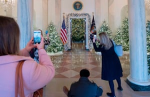 Visitors photograph Christmas trees in the grand foyer