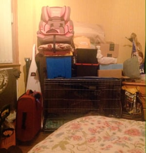 A bed in a junk room with a dog cage, a suitcase, a child's car seat and boxes