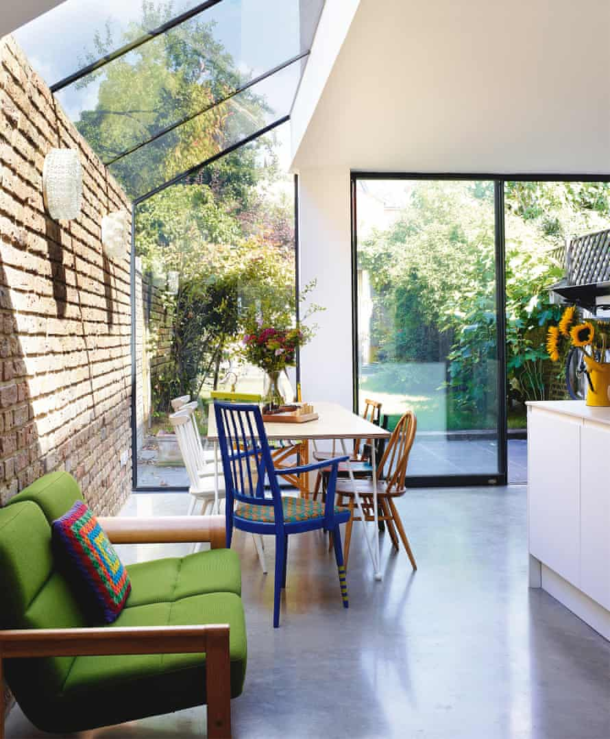 A bright, glass-roofed extension has replaced a gloomy side alley; the architects designed and made the tabletop with metalworkers geblondon.com; the blue chair is by Yinka Ilori and the Danish sofa from sunburyantiques.com.