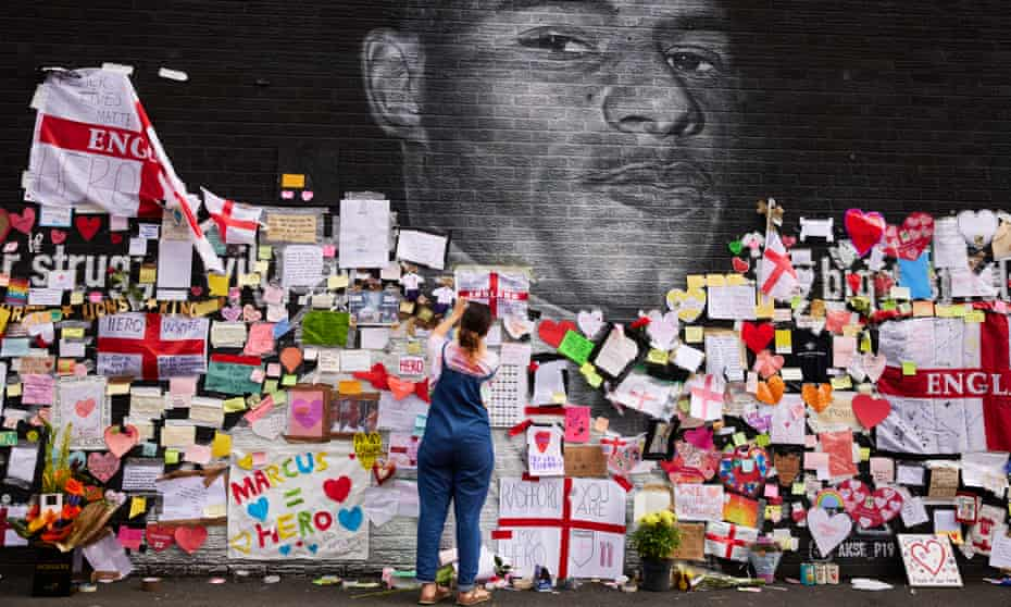 People look at the messages of support and the newly repaired mural of Marcus Rashford in Withington.