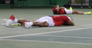 Rafa Nadal and partner Marc Lopez, of Spain, fall on the court after winning the gold.