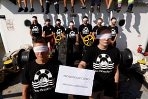 Protesters on a ship all wear white blindfolds