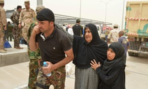 A tribal fighter helps civilians who fled Falluja during the offensive against Islamic State