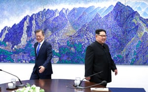 Kim and Moon walk back to their seats after a photo session in the Peace House
