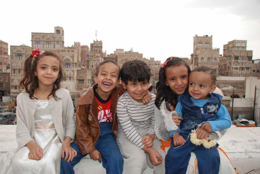 Five smiling children are photographed on the roof of a building, with the cityscape behind them.